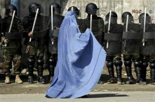 File photo of woman walking past riot police outside a gathering in Kabul's stadium